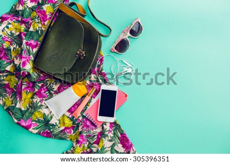 Close up lifestyle photo of hipster student accessories . Still life of random objects of modern girl / woman. Leather bag, camera, Sunglasses,t, Aerial view. Sunny summer colors.  Tropical print. - stock photo