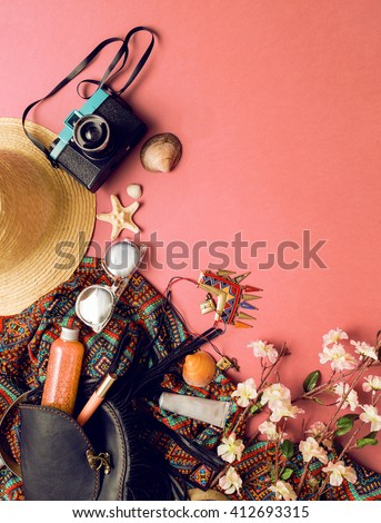 Close up lifestyle photo of woman traveler  accessories .Still life random objects  .Leather bag, camera,cool sunglasses. Aerial view. Sunny summer colors. Tropical print. Boho style.  - stock photo