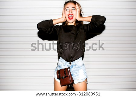 Close up lifestyle portrait of bad girl hipster girl making funny face and showing her tongue.Laughing portrait,crazy mood,covers ears and shouts,beats,beat box,music speakers,loud music,deep house - stock photo