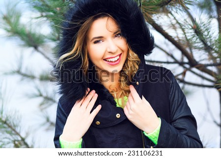 Close up lifestyle portrait of happy cheerful woman having fun alone at winter day, have red hairs bright make up and amazing smile.Wearing nice stylish jacket with fur, neon sweater. Holliday mood. - stock photo