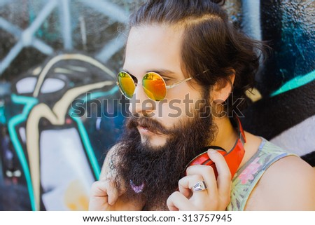 Close-up lifestyle portrait of man outdoors portrait.man posing on the wall,ready to trip. active.mans hairstyle.trendy man sunglasses,Young sportsman,young dj,t-shirt and shorts,Cool man with beard - stock photo