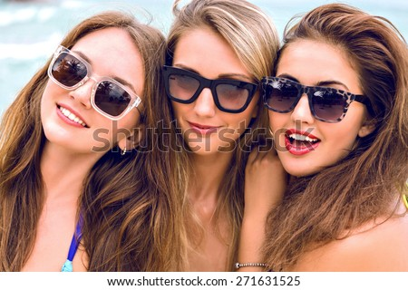 Close up lifestyle portrait of thee young stunning women with long hairs perfect skin and bright bikinis, posing on the beach at nice sunny summer day, having great time together. - stock photo