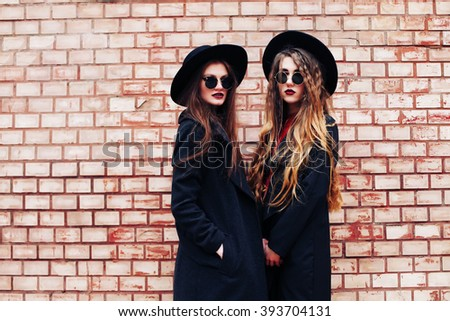 Close up lifestyle portrait of two best friends, having fun together, wearing trendy wool hat, round sunglasses, stylish vintage bohemian outfits. Shopping day. Photo toned style instagram filters. - stock photo