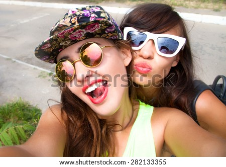 Close up lifestyle portrait of two pretty fresh hipster young brunette and blonde best friends girls,make selfie and having fun.Wear summer sunglasses and make photos,of their weekends.Selfie portrait - stock photo