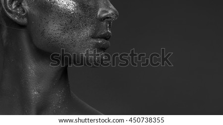 Close-up lips and neck vogue style portrait of a woman. Black makeup with glitter. Dark background. Black and white