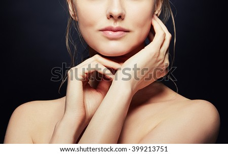 Close-up lips and shoulders of beautiful caucasian blonde woman isolated on black background. Studio portrait. Toned - stock photo