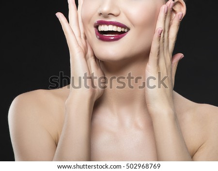 Close-up lips and shoulders of caucasian brunette woman with wet red lipstick and arms touching face with smile. Isolated on black background.