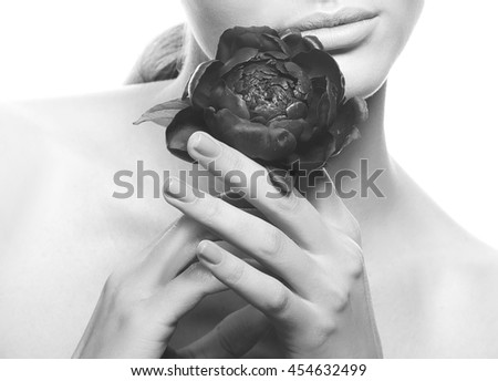 Close-up lips and shoulders of caucasian young brunette woman with peony flower in hand. Studio portrait. Isolated on white background. Black and white - stock photo