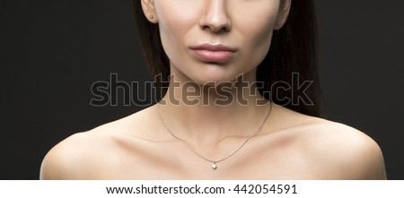 Close-up lips and shoulders of young brunette caucasian attractive sad woman with natural make-up. Studio portrait.  - stock photo