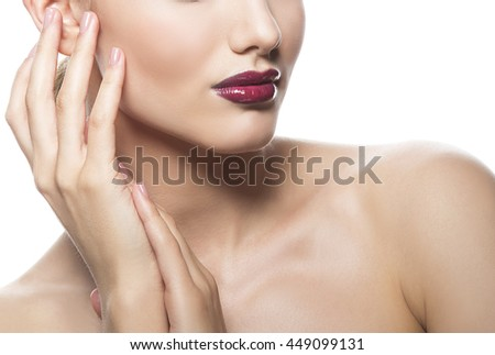 Close-up lips and shoulders of young caucasian brunette woman with red glossy lips, intensive make-up, perfect skin and blue eyes isolated on white touch her skin. Studio portrait.  - stock photo