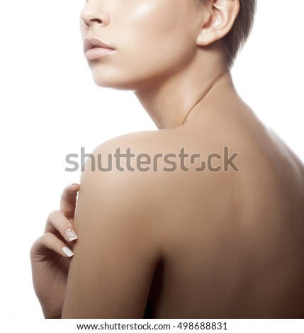 Close-up lips and shoulders of young caucasian girl with natural make-up, perfect skin and green eyes touch her skin isolated on white background. Studio portrait.