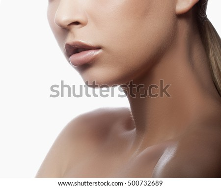 Close-up lips and shoulders of young caucasian girl with natural make-up, perfect skin and green eyes over white background. Studio portrait