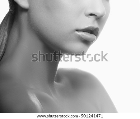Close-up lips and shoulders of young caucasian girl with natural make-up, perfect skin and green eyes over white background. Studio portrait. Black and white