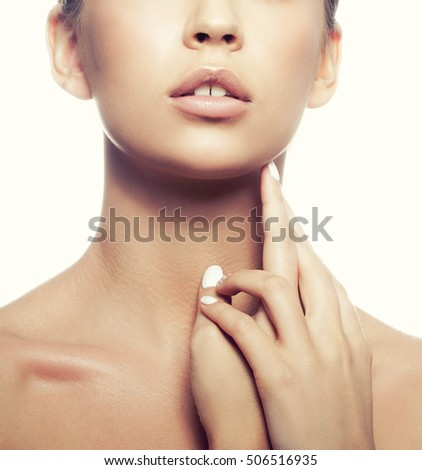 Close-up lips and shoulders of young caucasian girl with natural make-up, perfect skin and green eyes isolated on white background. Studio portrait. Toned