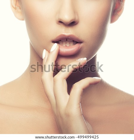 Close-up lips and shoulders of young caucasian girl with natural make-up, perfect skin touch her skin isolated on white background. Studio portrait. Toned