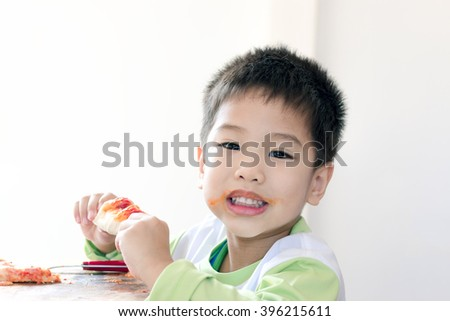 Close up little Asian boy eats pizza on white background - stock photo