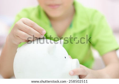 Close up Little boy saving money in piggy bank  - stock photo