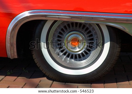 Close-up look at a classic car with chrome and white wall tires. - stock photo