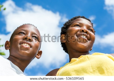Close up low angle face shot of two african kids against blue sky and cloud background.