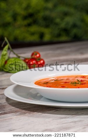 Close-up low-angle picture of cold tasty tomato soup gazpacho with species on the wooden table in vegan caffee with tomatoes standing near a plate, with copy place and selective focus on a plate - stock photo