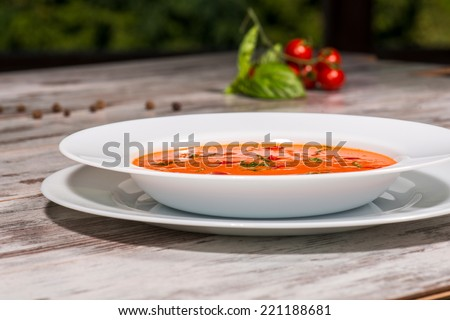 Close-up low-angle picture of cold tasty tomato soup gazpacho with species on the wooden table in vegan cafe with tomatoes standing near a plate, with copy place and selective focus on a plate - stock photo