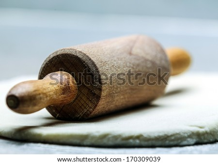 Close-up low angle view of an old-fashioned wooden rolling pin on rolled out dough or pastry resting at an oblique angle with the handle towards the camera and shallow dof - stock photo