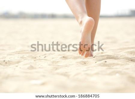Close up low angle woman barefoot walking on beach - stock photo