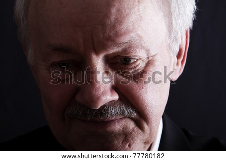 Close up low key portrait of a senior business man with serious depression. - stock photo