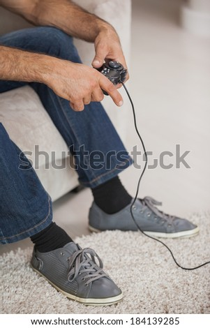 Close-up low section of a man playing video games in the living room at home - stock photo