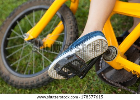 Close-up low section of a young boy with bicycle at the park