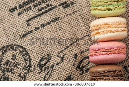Close up macaroons on the jute tablecloth with space - stock photo