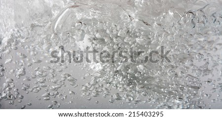 Close up macro background detail of silver gray metallic mercury water liquid in motion, moving and shining with air bubbles. Still life of water texture and detail. - stock photo
