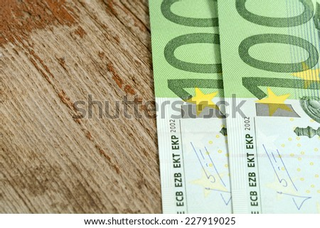 Close up macro detail of euro money banknotes on wooden plank