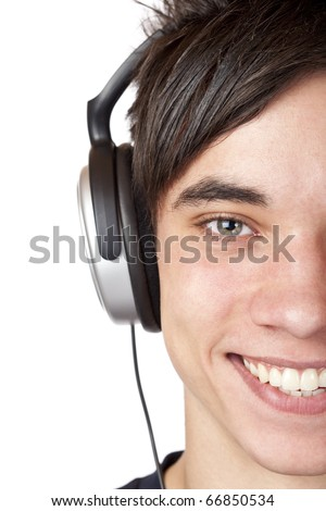 Close-up macro of a male teenager listening to music with headphone. Isolated on white.