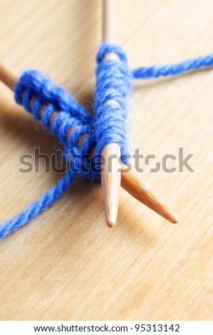 Close up (macro) of a pair of crossed  knitting needles laid on a wooden table holding stitches in pale blue wool. - stock photo