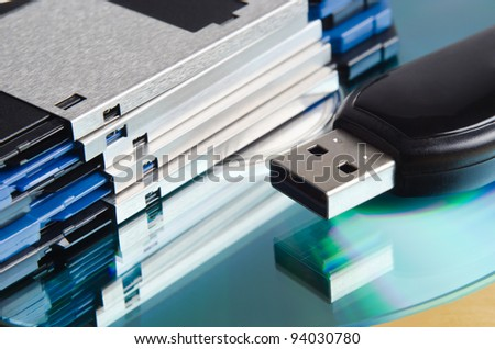 Close up (macro) of a selection of old and new storage media.  Three and a quarter inch floppy disks, CD-ROM and USB memory stick. - stock photo