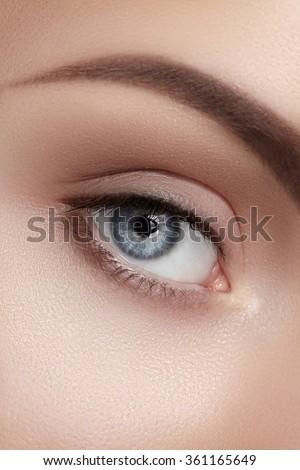 Close-up macro of beautiful female eye with perfect shape eyebrows. Clean skin, fashion naturel make-up. Good vision - stock photo