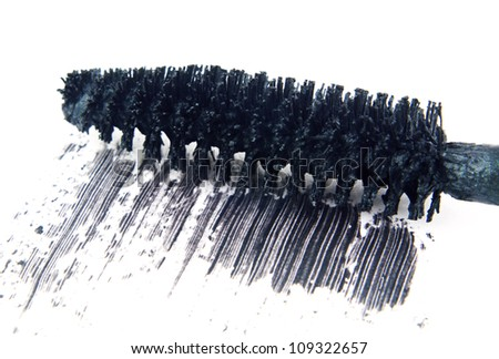 Close up macro of black mascara makeup brush wand with smear isolated on white background with copy space.