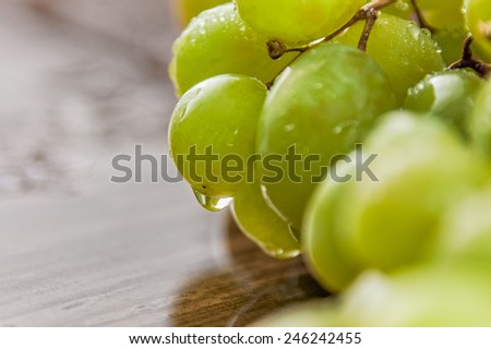 Close up macro of wet green grapes on a wooden table - stock photo