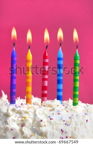 Close up macro photograph of 5 candles on a birthday cake - stock photo