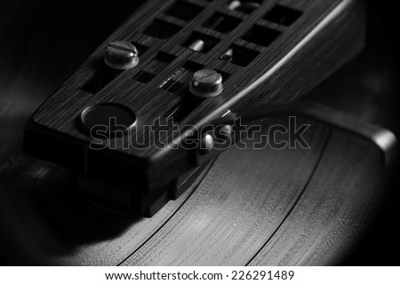 Close up magnification of a vinyl record playing in black and white - stock photo