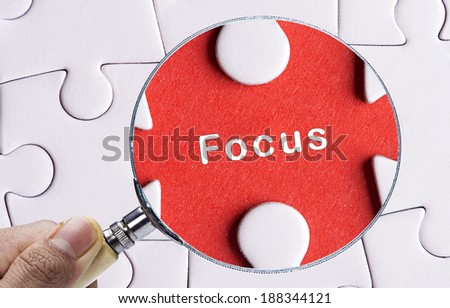 """Close up Magnifying glass searching missing puzzle peace """"FOCUS"""" - stock photo"""