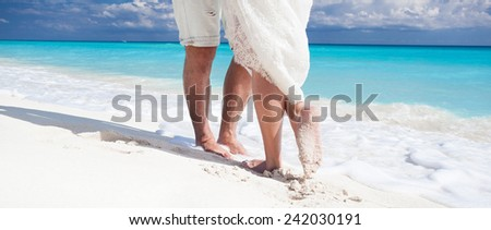 Close up male and female feet on white sand, kissing - stock photo