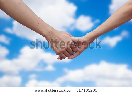 close up male and female hands holding together on blurred blue sky  background.passion in love concept ,soft focused.picture use for work about decorate,design.happy family concept.healthcare family. - stock photo