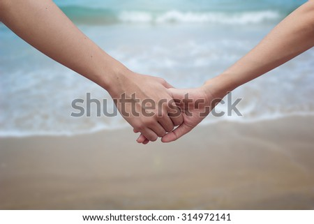 close up male and female hands holding together on blurred sea and beach background.passion in love concept ,soft focused.picture use for work about decorate,design,wedding,card,valentines and etc.  - stock photo