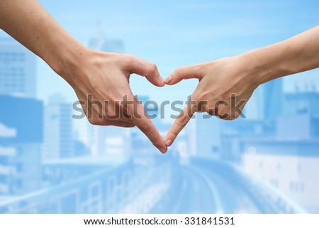 close up male and female hands making heart on blurred blue cityspace backgrounds . love city concept,soft focused.picture for work about decorate,design,religious,valentines,wedding and etc. - stock photo