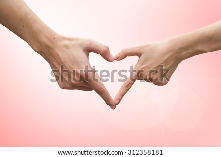 close up male and female hands making heart on blurred bright soft pink colors backgrounds . passion in love concept ,soft focused.for work about decorate,design,wedding,card,valentines and etc. - stock photo