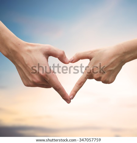 close up male and female hands making heart on blurred morning sky sunrise backgrounds.passion in love concept,soft focused.picture for work about decorate,design,religious,valentines,wedding and etc.
