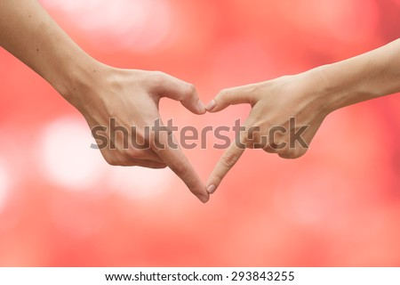 close up male and female hands making heart on blurred pink backgrounds . passion in love concept ,soft focused - stock photo