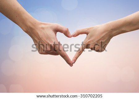 close up male and female hands making heart on blurred vintage colors backgrounds . passion in love concept ,soft focused.picture use for work about decorate,design,wedding,card,valentines and etc.  - stock photo